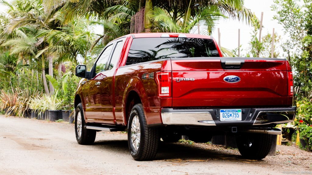 A Cherry Red Ford F150 pickup truck parked in front of some palm trees.