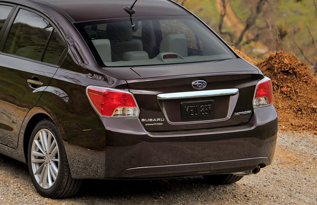 The rear end of a plum 2013 Subaru Impreza sedan.