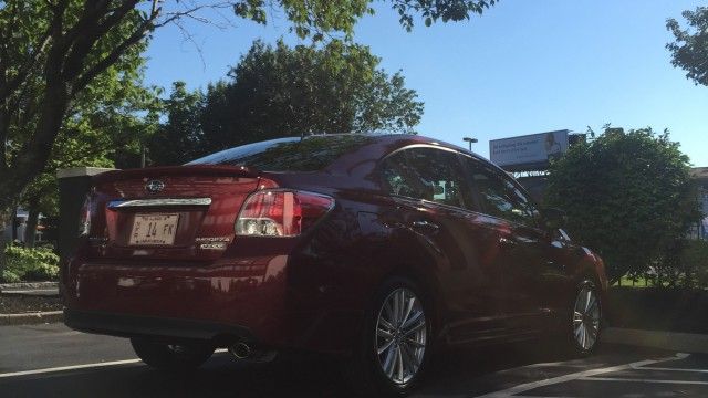 Rear view of a red 2015 Subaru Impreza sedan